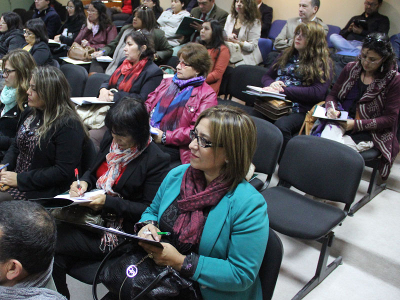 En primer plano, una docente observa sonriente la actividad.