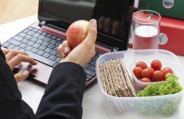 Una mano sostiene una manzana en un escritorio de trabajo, junto a un recipiente con verduras.