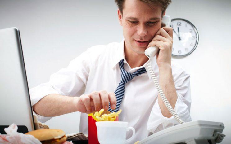 Oificinista come papas fritas sentado en su escritorio mientras habla por teléfono.