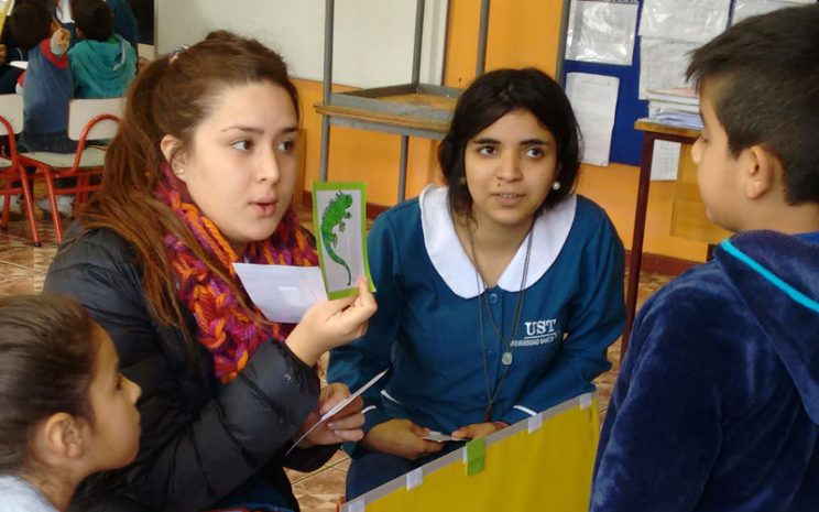 Niño observa lámina con dibujo que es mostrada por una de las alumnas.
