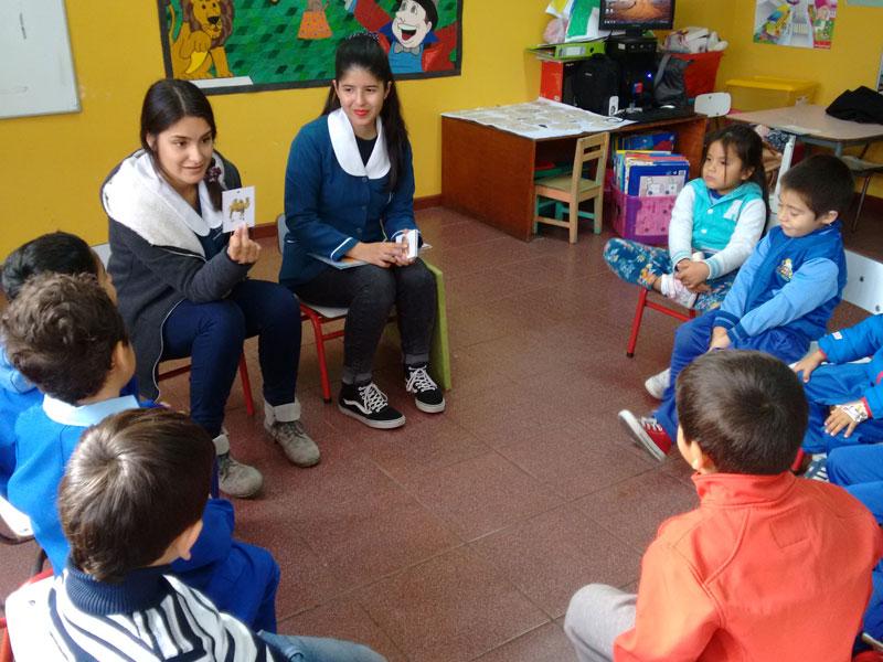 Dos estudiantes desarrollan un trabajo grupal con los niños sentados en círculo.