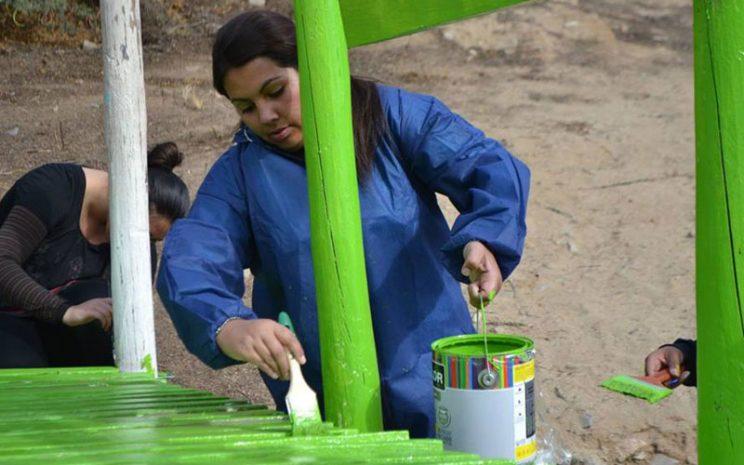 Una estudiante pinta de color verde uno de los juegos de la escuela.
