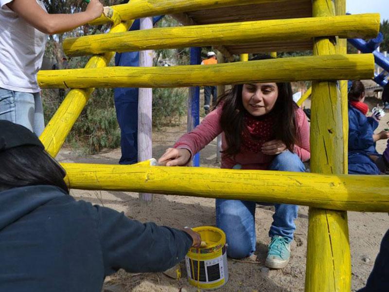 Una alumna pinta de color amarillo uno de los juegos.