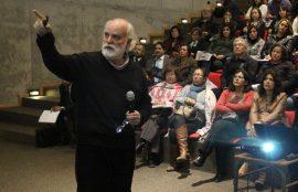 Sergio Canals en primer plano, explica y apunta a su presentación en pantalla mientras lo observa la audiencia.