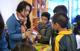 Tres niños observan una tarjeta didáctica que les muestra una estudiante.