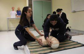 Estudiante de Enfermería enseña a una participante técnicas de reanimación con un muñeco.