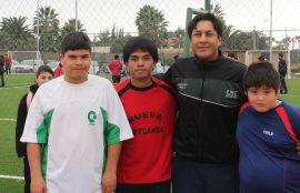 Profesor Luis Veas junto a tres niños.