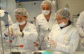 Una estudiante y una beneficiaria del taller, observan el trabajo con tubos de ensayo de otra compañera.