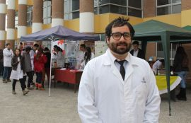 Sebastián Meneses en primer plano, y al fondo, la expo química.