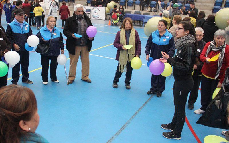 Adultos mayores, con globos de colores en las manos, escuchan las indicones de una estudiante.