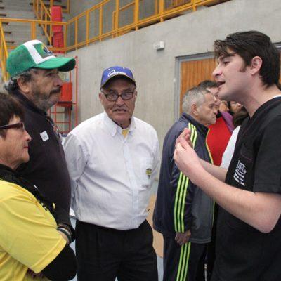 Estudiante de Kinesiología entrega consejos a dos participantes.