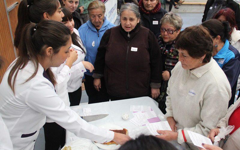 Alumna de Nutrición y Dietética entrega consejos a una participante de la actividad.
