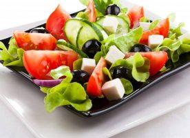 Plato de ensalada con verduras verdes, tomates, aceitunas y queso.