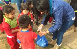 Una de los estudiantes participantes de los proyectos sostiene una bolsa para que dos niños introduzcan basura a reciclar.