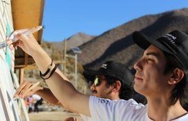 Dos jóvenes pintan un muro.