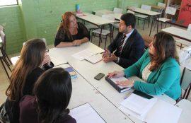 Cuatro estudiantes de la carrera dialogan y aconsejan en materias juridícas a una apoderada.