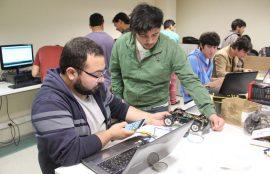 Dos estudiantes controlan un pequeño robot con ruedas mediante un teléfono celular.