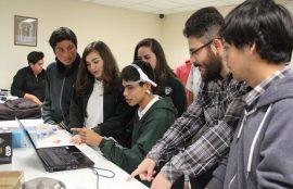 Estudiantes de Informática enseñan la utilización de un sensor a un alumno del Colegio Santo Tomás.
