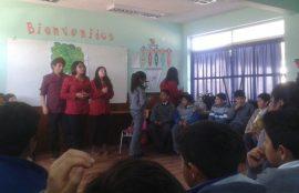 Tres estudiantes hablan con estudiantes en una de las salas de los colegios.