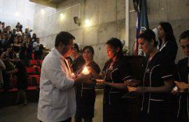 Director de Escuela, Rodrigo Ardiles, enciende las lámparas de las alumnas durante el acto.