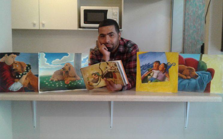 Roberto junto a algunos de sus libros e ilustraciones.