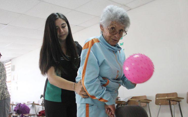 Adulta mayor es apoyada por una alumna de Kinesiología durante un ejercicio con balón.