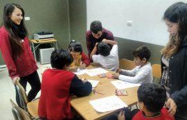 Tres estudiantes de Psicología supervisan trabajo grupal de 5 niños.