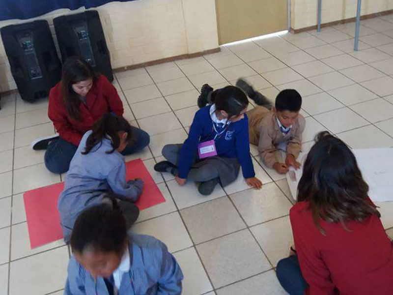Niños dibujan en el suelo, mientras observan dos alumnos de Psicología.