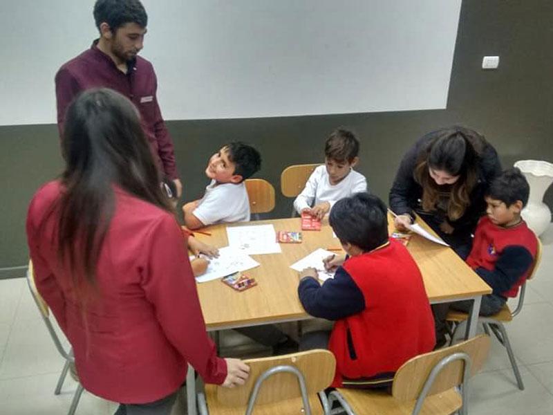 Tres niños dibujan sentados en una mesa, supervisados por tres alumnos de Psicología.