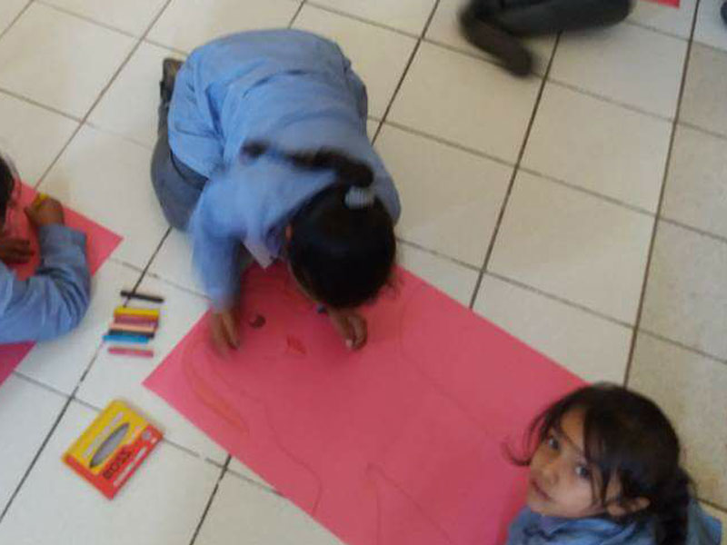 Niñas dibujan y pintan en el suelo.