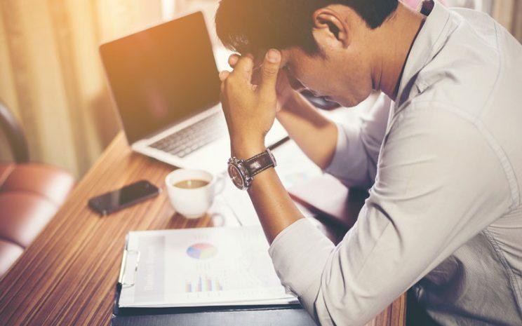 Hombre se toma la cabeza en signo de estrés, sobre su escritorio.