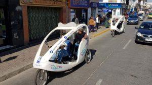 Dos triciclos del proyecto recorriendo la calle.