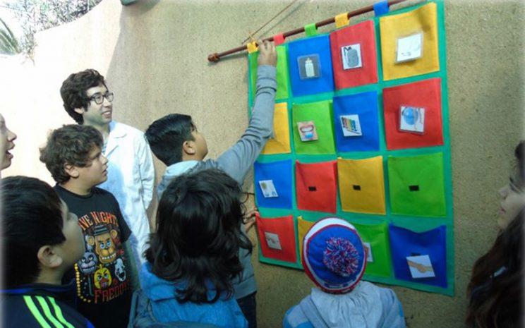 Grupo de niños trabajan y juegan con material confeccionado por alumnos de la carrera.