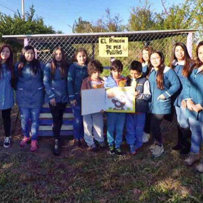 Grupo de alumnas junto a tres estudiantes de escuela donde se construyó un gallinero.