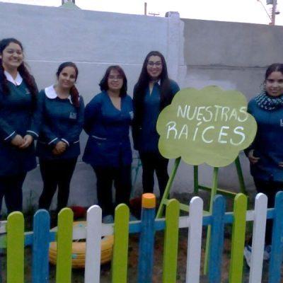 Cinco alumnas junto a cartel que dice Nuestras raíces.