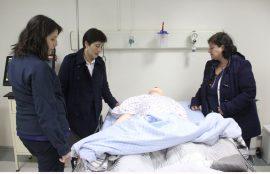 Tres de las enfermeras observan maniquí de enfermo acostado en camilla.