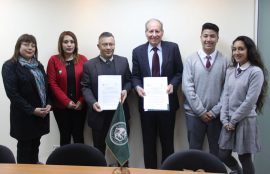 Rectores de ambas instituciones junto a los asistentes a la firma del convenio.