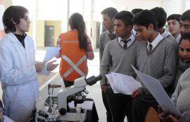 Estudiante de química atendiendo preguntas de escolares en stand.