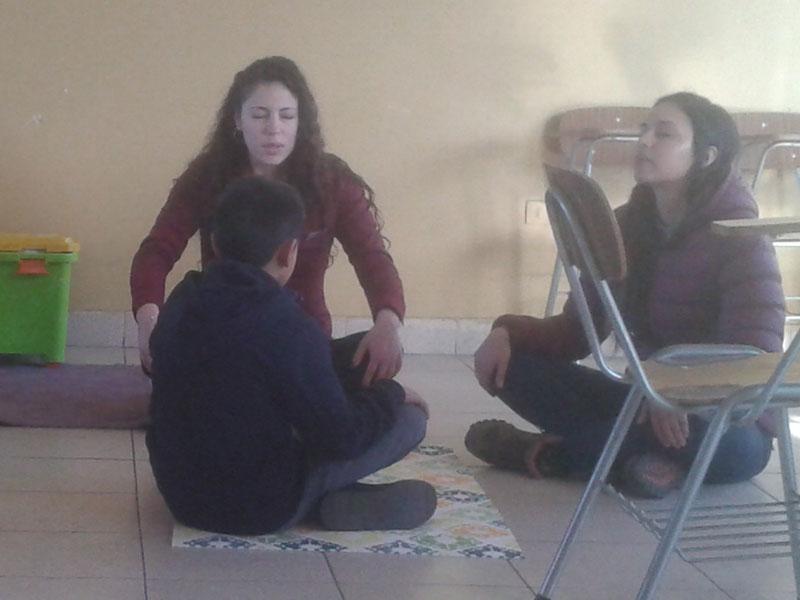 Alumnas realizando dinámica de relajación con un niño.