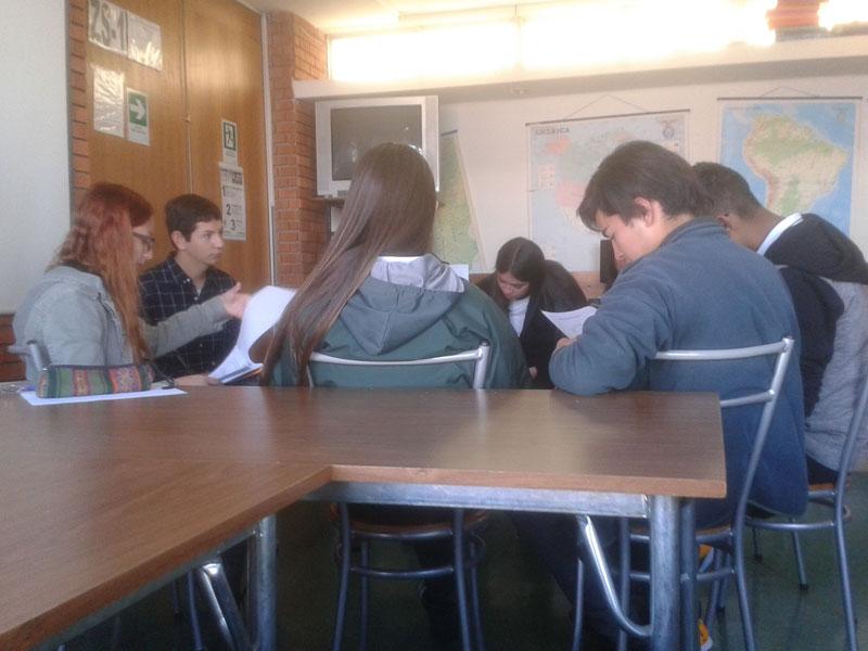 Jóvenes trabajan en dinámica grupal junto a dos estudiantes de Psicología.