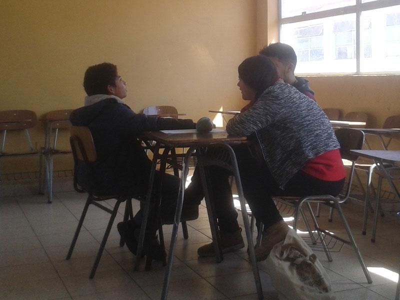 Niño trabaja en una mesa junto a dos alumnos de Psicología.
