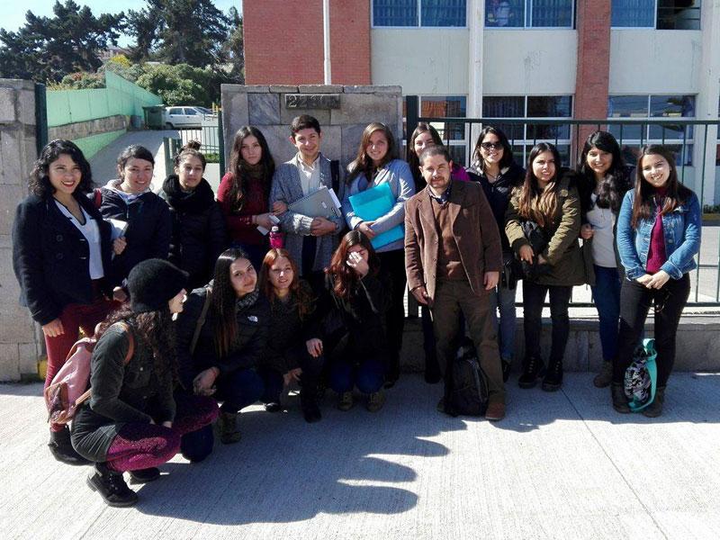 Grupo de estudiantes junto a profesor Francisco Araya en frontis de colegio Santo Tomás.