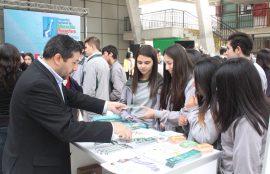 Estudiantes reciben volantes de información en uno de los stands.