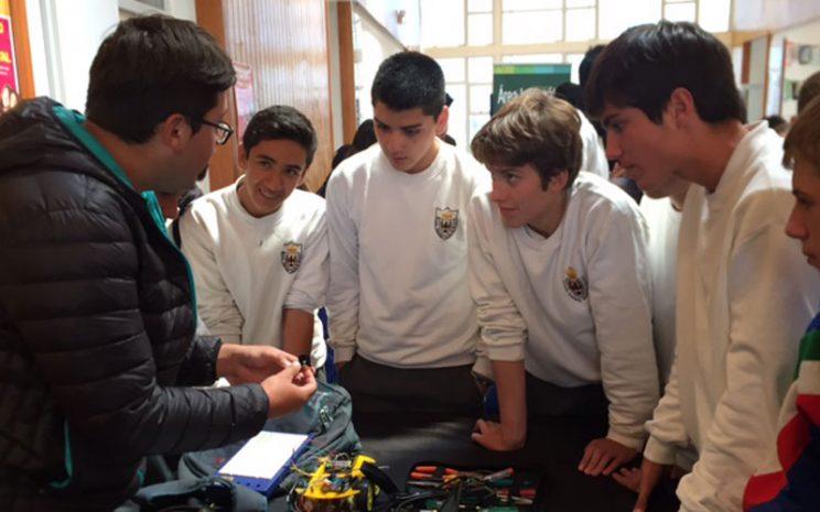 Cuatro alunnos del colegio observan explicación de un estudiante de Informática.