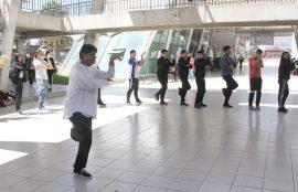 Profesor liderando postura de brazos y pierna en Clase de Tai Chi.