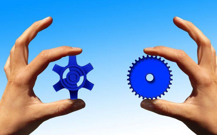 Dos manos sostiene dos engranajes de mismo color pero distinta forma.