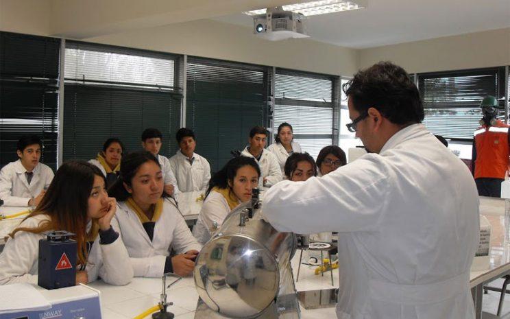 Docente enseña detalles de un experimento a estudiantes.