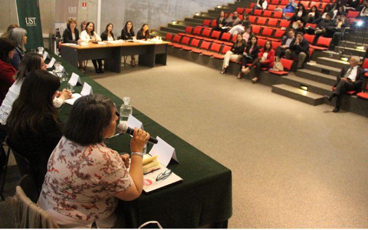 Vista lateral donde se aprecia mesa de candidatas, mesa de panel de moderadoras y parte del público.