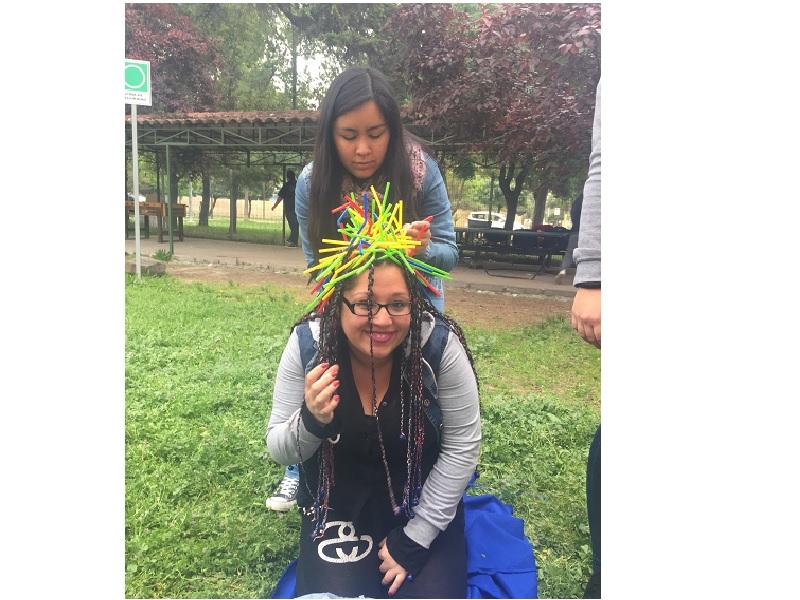 Una joven con lentes sonríe mientras su compañera le pone bombillas en el cabello, como parte de un juego.