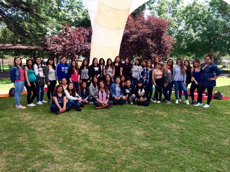 Alumnas del área de educación agrupados en la cancha de pasto, bajo un toldo blanco.